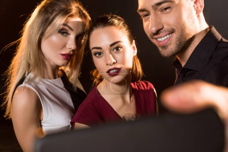 close-up shot of group of people taking selfie with smartphone during party on black