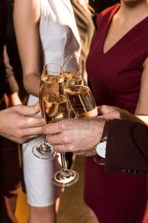 cropped shot of friends clinking champagne glasses during holiday party