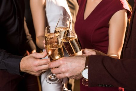 Photo pour Recadrée tir d'amis tinter les verres de champagne au cours de la partie - image libre de droit