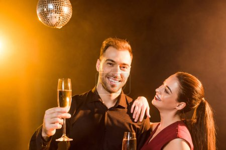 happy young couple holding champagne under golden light
