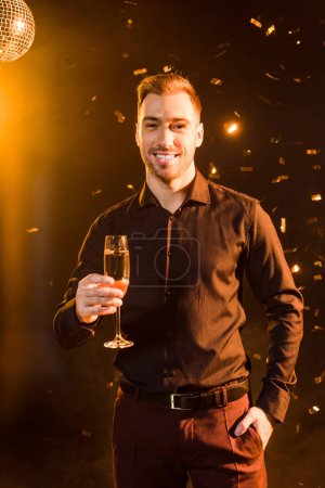 handsome young man with glass of champagne under yellow light on black