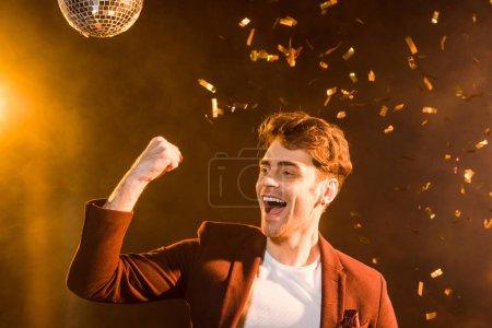 Photo pour Heureux jeune homme célébrant sous tomber confettis sur noir - image libre de droit