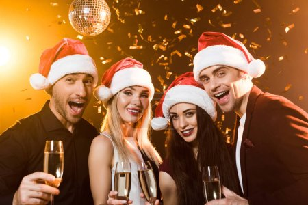 group of smiling friends in santa hats holding glasses of champagne and looking at camera