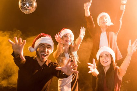 Photo for Group of friends in santa hats celebrating new year under yellow light - Royalty Free Image