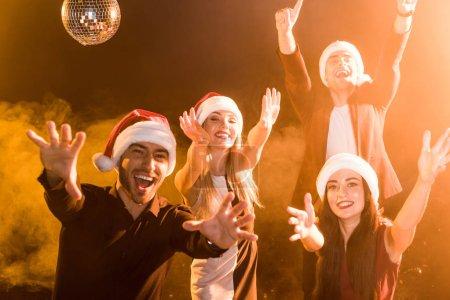 Photo pour Groupe d'amis dans chapeaux de Père Noël célébrant le Nouvel An sous la lumière jaune - image libre de droit