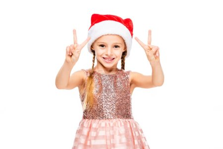 adorable little child in santa hat showing peace signs at camera isolated on white