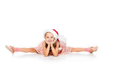adorable little child in santa hat sitting splits on floor and looking at camera isolated on white