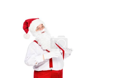 emotional santa claus in suspenders looking at camera isolated on white