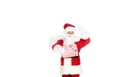 santa claus holding gift box and gesturing at camera isolated on white