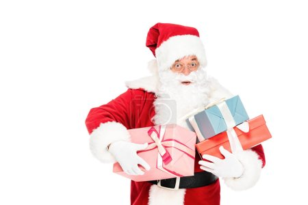 santa claus holding pile of gift boxes and looking at camera with shocked expression isolated on white