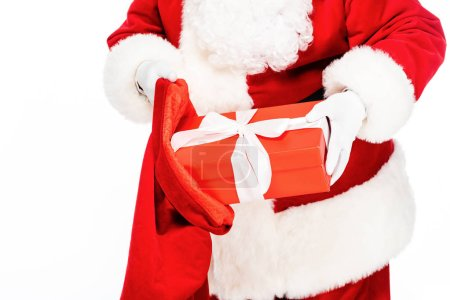 cropped shot of santa claus putting present into bag isolated on white