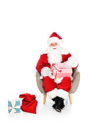 santa claus sitting in armchair with various gift boxes isolated on white