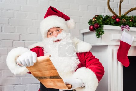santa claus holding parchment and reading wish list