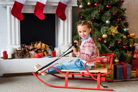 Photo pour Mignon enfant heureux assis sur le traîneau et souriant à la caméra près de cheminée - image libre de droit