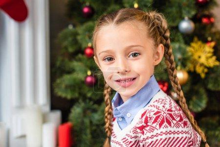 Photo pour Portrait de l'adorable gamin heureux, souriant à la caméra au moment de Noël - image libre de droit