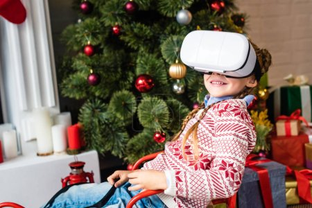 cute smiling child sitting in sled and using virtual reality headset at christmas time