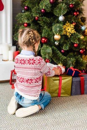 Photo pour Vue arrière des boîtes-cadeaux d'ouverture d'enfant mignon sous l'arbre de Noël - image libre de droit