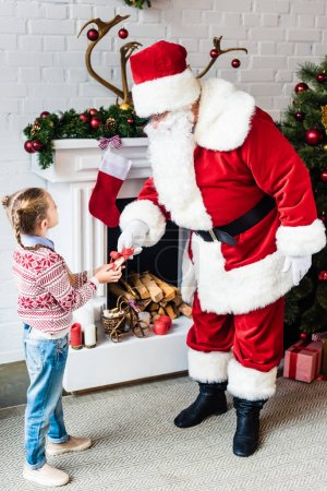 high angle view of little child giving rolled wishlist to santa