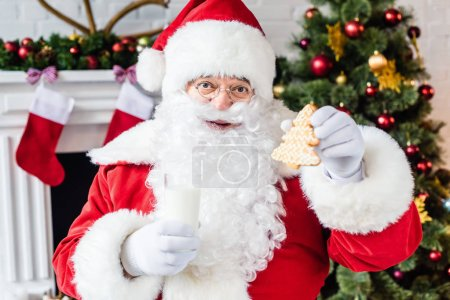 happy santa claus holding gingerbread cookie and glass of milk