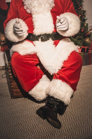 cropped host of santa claus with open arms sitting on old chest