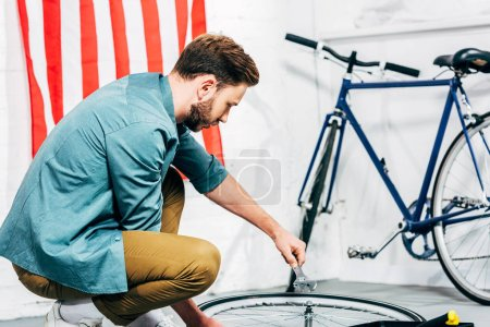 concentrated repairman with adjustable wrench in hand fixing bicycle