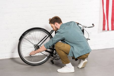 Photo for Side view of young man repairing bicycle by adjustable spanner - Royalty Free Image