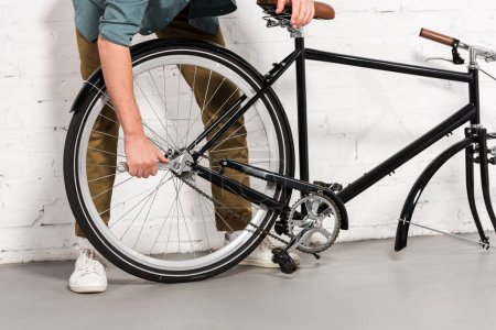 cropped image of young man repairing bicycle by adjustable spanner