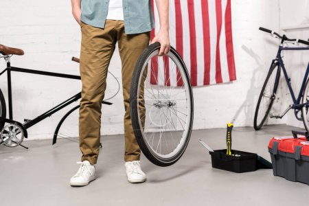 cropped image of man holding bicycle wheel in hand