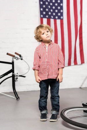 Photo for Adorable little boy looking at camera near disassembled bicycle at workshop - Royalty Free Image
