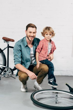 Photo for Happy man sitting with little son and looking at camera in bicycle workshop - Royalty Free Image