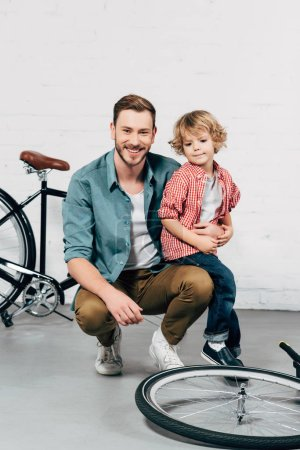 cheerful handsome man sitting with little son and looking at camera in bicycle workshop
