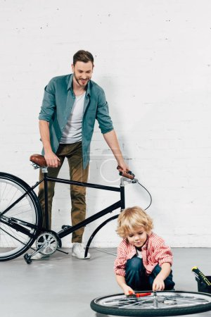 Foto de Adorable niño rueda por alicates mientras su padre está parado detrás con bicicletas desmontadas en taller de fijación - Imagen libre de derechos