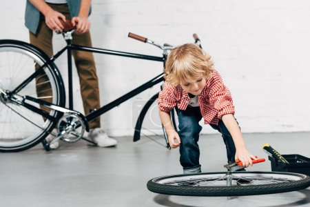 joyful little boy fixing wheel by pliers while his father standing behind with disassembled bicycle in workshop