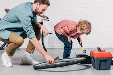 side view of male repairman fixing bicycle wheel with pliers while his little son standing near with tools box in workshop