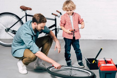 male repairman fixing bicycle wheel with pliers while his little son standing near in workshop