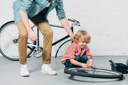Photo for Cropped image of man standing near little son fixing wheel by pliers at bicycle workshop - Royalty Free Image