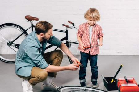 selective focus of repairman fixing bicycle wheel with pliers while his little son standing near with screwdriver in workshop