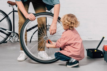 Photo for Cropped image of father holding bicycle wheel while his little son repairing with pliers at workshop - Royalty Free Image