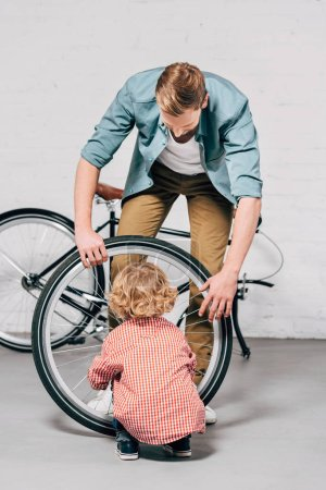 rear view of little boy repairing bicycle wheel while his father helping at workshop