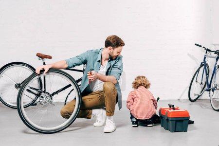 Foto de Alegre reparador masculino sosteniendo destornillador y mirando al pequeño hijo sentado cerca con cajas de herramientas en el taller - Imagen libre de derechos