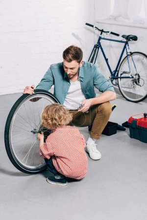 Photo for High angle view of father holding bicycle wheel while his little son repairing at workshop - Royalty Free Image