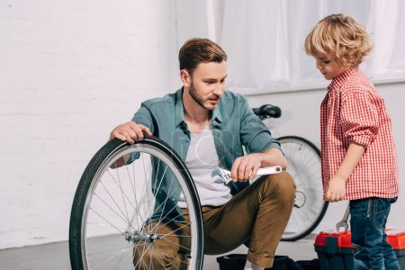 Photo for Man with adjustable spanner sitting near bicycle wheel and talking to little son in workshop - Royalty Free Image