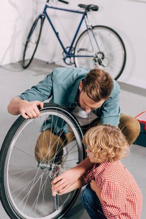 Photo for High angle view of repairman showing how to fixing bicycle wheel with adjustable spanner to little son in workshop - Royalty Free Image