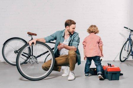 Foto de Enfoque selectivo de reparador hombre sentado junto a la rueda de bicicleta y mirar hijo junto a cajas de herramientas en el taller - Imagen libre de derechos
