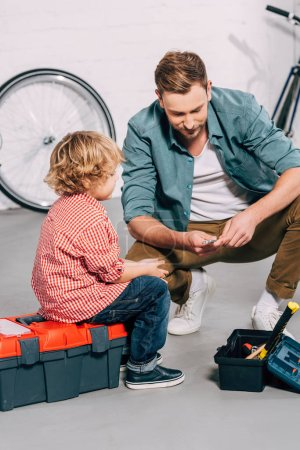 Photo for Joyful man showing spanner to little son at bicycle workshop - Royalty Free Image