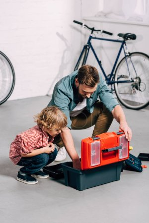 high angle view of father and adorable little son sitting near opened tools box in bicycle workshop
