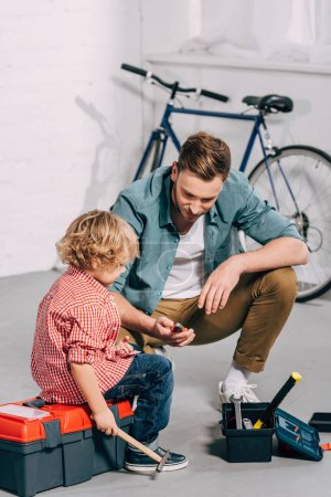 Photo for Man holding pliers and sitting with little son sitting near opened tools boxes in bicycle workshop - Royalty Free Image