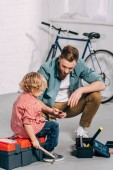 man holding pliers and sitting with little son sitting near opened tools boxes in bicycle workshop
