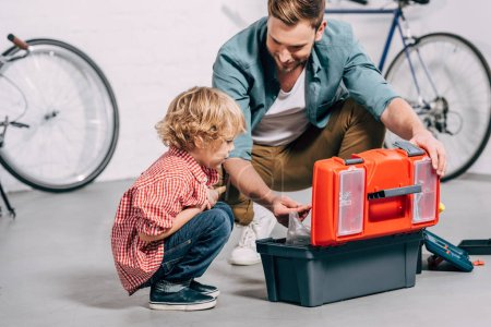 Photo for Father and adorable little son sitting near opened tools box in bicycle workshop - Royalty Free Image
