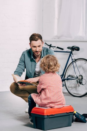 Photo for Man talking and reading book to little son sitting on tools box in bicycle workshop - Royalty Free Image